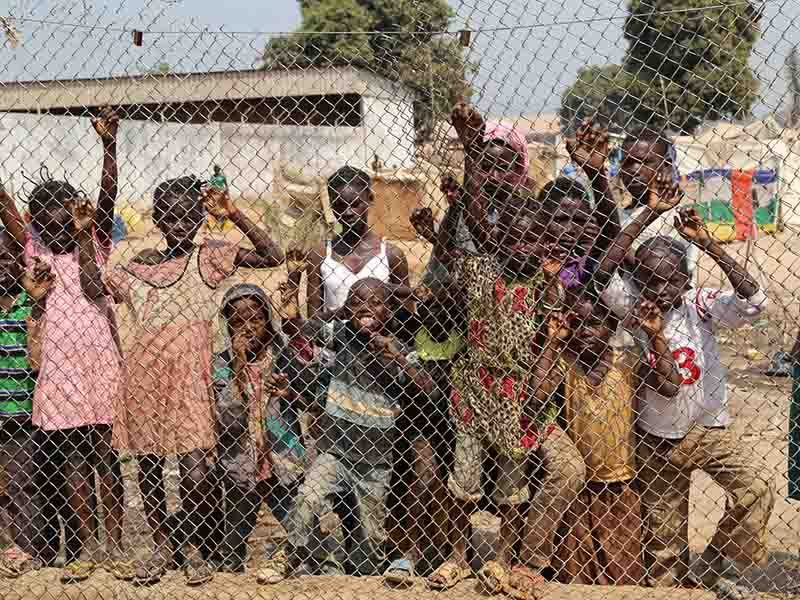 Photo of kids against a fence at the airport in Central African Republic